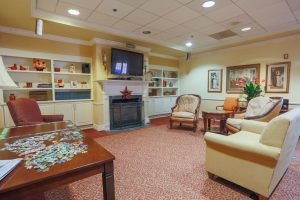 Charter Senior Living of Towson - Living Room with puzzle on table - couches - tv